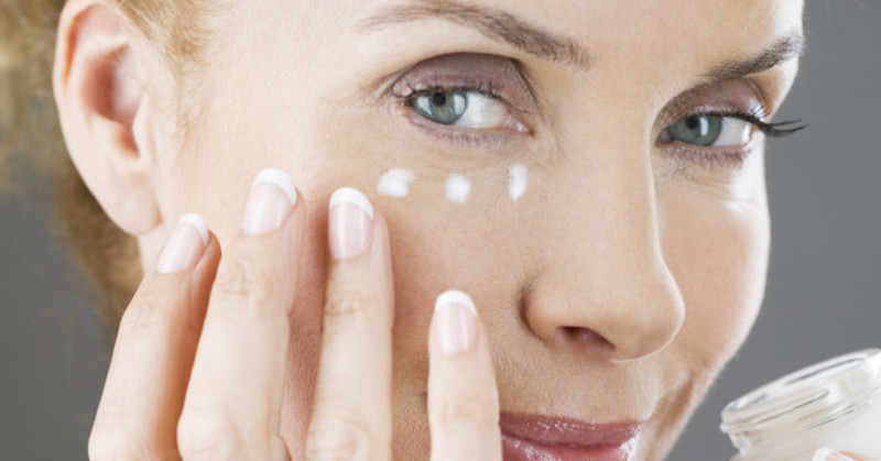 woman applying cream on wrinkles