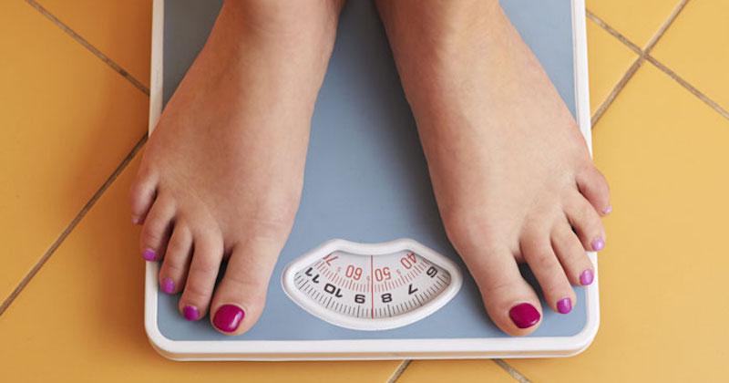 woman's feet on bathroom scale