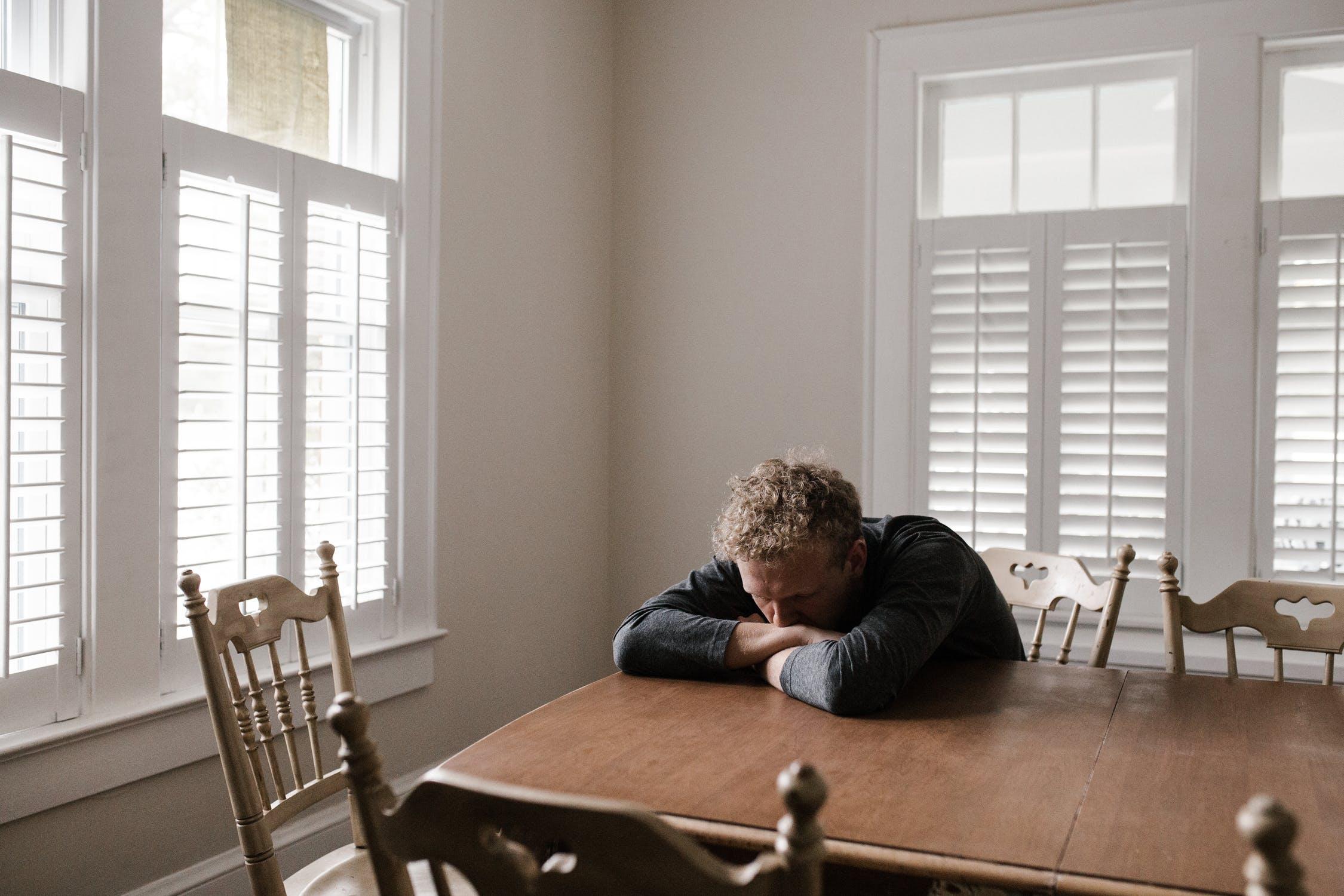 Unhappy man sitting at table